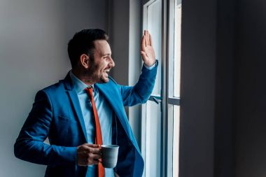 businessman greeting friend through window.