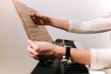 female hand holding classical sheet music for piano playing