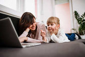 Cute little girl pointing at laptop screen while watching cartoons with her mother.