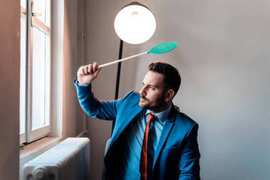 Attractive businessman with fly swatter. Annoyed man in a suit hitting a fly with fly swatter.
