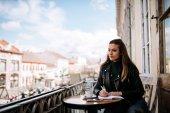 Krásná dívka studující venku v kavárně.