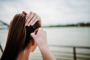 Woman putting bobby pins in hair outdoors