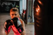 Photo Close-up image of serious boxer girl practicing on a large bag.