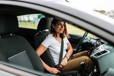 young woman in casual wear driving carac