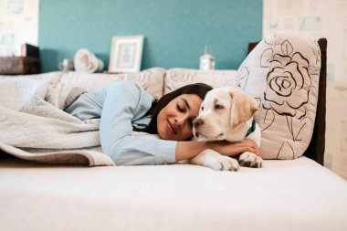 Attractive young woman with dog laying on bed