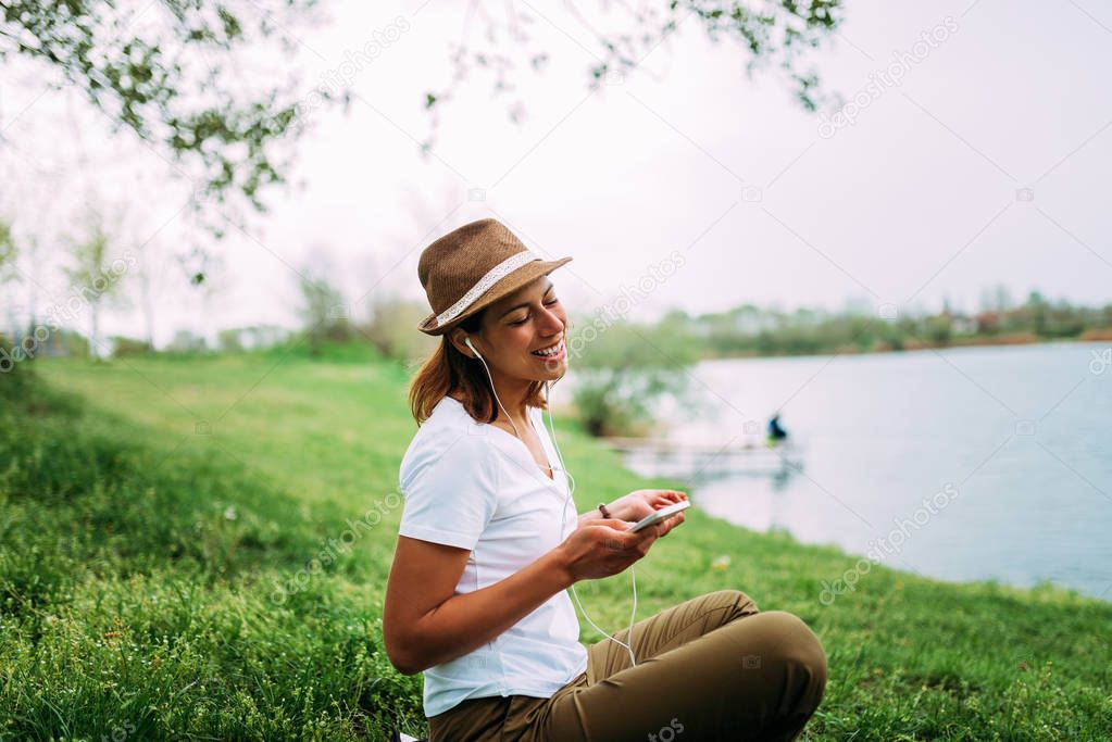 Cheerful woman in headphone holding smartphone and listening to music while sitting on grass