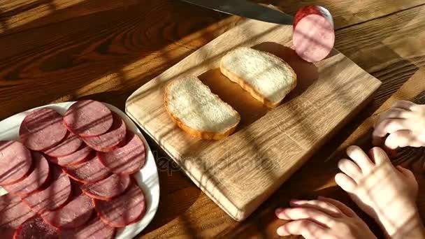 Krájení klobása na prkně. Hovězí párky. Řez s kuchyňským nožem. Léčbě sendvič