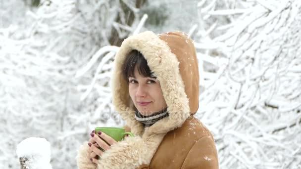 Dívka s šálkem čaje se dívá na padající sníh v zimě. Husté sněžení. Krásné zimní.