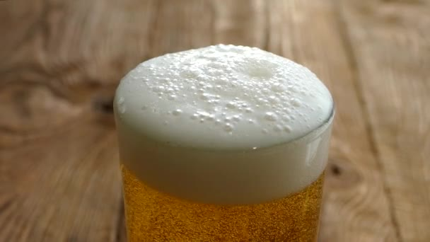 Nalijte čerstvé pivo ve sklenici na dřevěný stůl. Pivní pěna se přelije ze skla. Jeho světlo na stůl