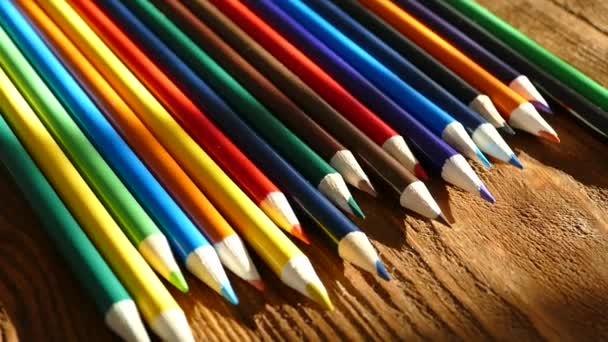 Barevné tužky ve sklenici psaní. Kreslit pastelkami na bílém papíře a dřevěný stůl. Dřevěný stůl retro.