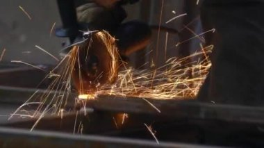 A person works with a grinder. Cuts steel structures in the factory. Beautiful sparks fly out
