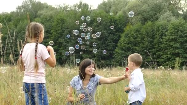 Happy family playing in nature. Mom and children are blowing bubbles. A girl and a boy are playing with her mother. Camping with the family. Glade near the forest. The sun is shining and its raining.