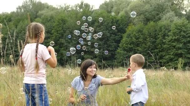 glückliche Familie spielt in der Natur. Mutter und Kinder pusten Blasen. ein Mädchen und ein Junge spielen mit ihrer Mutter. Zelten mit der Familie. Lichtung am Waldrand. die Sonne scheint und es regnet.