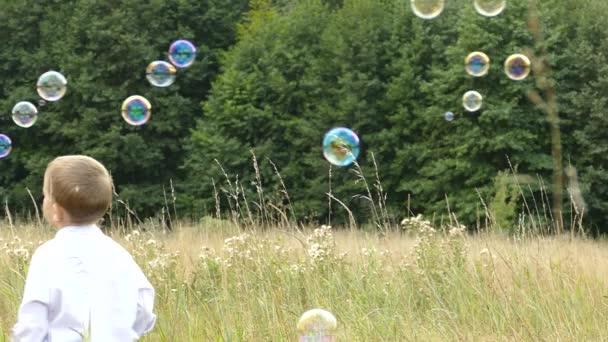 Boldog család, játszott a természetben. Anya és a gyermek a buborékokat. Egy lány és egy fiú játszik az anyja. Kempingezés a család. Tisztáson, az erdő közelében. Süt a nap, és esik az eső.