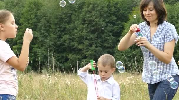 Šťastná rodina hraje v přírodě. Máma a děti jsou vyfukování bublin. Dívka a chlapec hraje s její matkou. Kempování s rodinou. Glade poblíž lesa. Svítí slunce a prší.