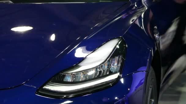 Parkovací světlo bliká ve vozidle. Modré sportovní auto. Elektromobil Tesla. Světla do auta