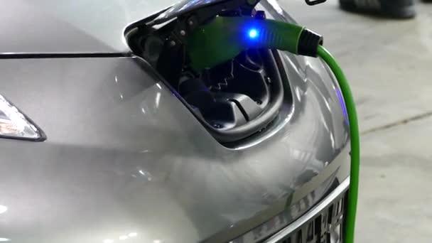 Az elektromos autó fel van töltve keresztül egy speciális outlet elektromos hálózatról. Csatlakozó egy elektromos autó töltés. Egy személy a elektromos autó a feltöltő. A csatlakozó be van dugva az aljzatnak. Ökológiai közlekedési mód. Jövőbeli tec