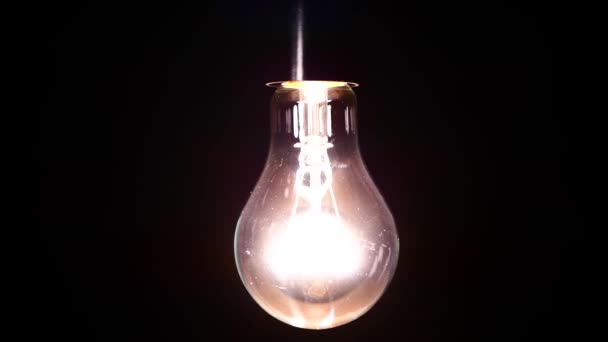 Žárovka s Wolframové vlákno se netočí na drátě. Světlo bliká v důsledku špatného kontaktu. Elektrické energie byl ztracen v místnosti. Světlo ze žárovky. Žárovka detail.