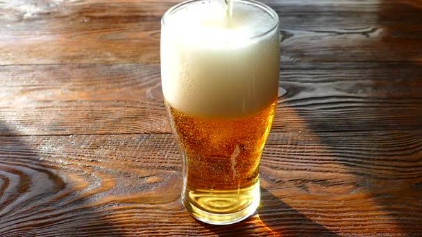 Pivo se nalije do skleněné sklenice. Lehké, nealkoholické nápoj žluté barvy. Krásné bublinky sycených nápojů. Sklenice pivní pěny na retro stolní desku.