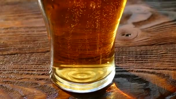 Beer is poured into a glass glass. Light, low-alcohol beverage of yellow color. Beautiful bubbles of a carbonated drink. A glass of foam beer on a retro table top.