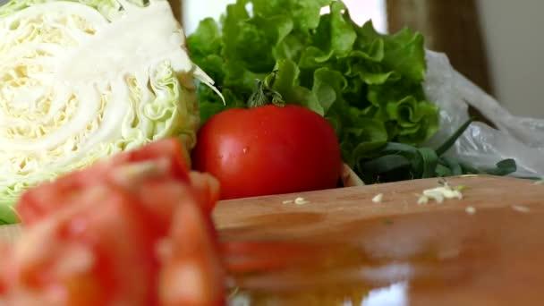 Fette di pomodoro e altre verdure su un tagliere in cucina. Cibo sano vegetariano