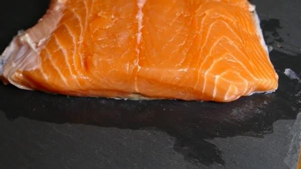 Krájené a loupané filety z lososa na řezací desce. Osolte rybí filé. Uvař v kuchyni rybí misku..