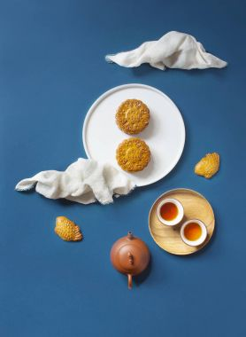 Conceptual flat lay mid-autumn festival food still life on blue background.