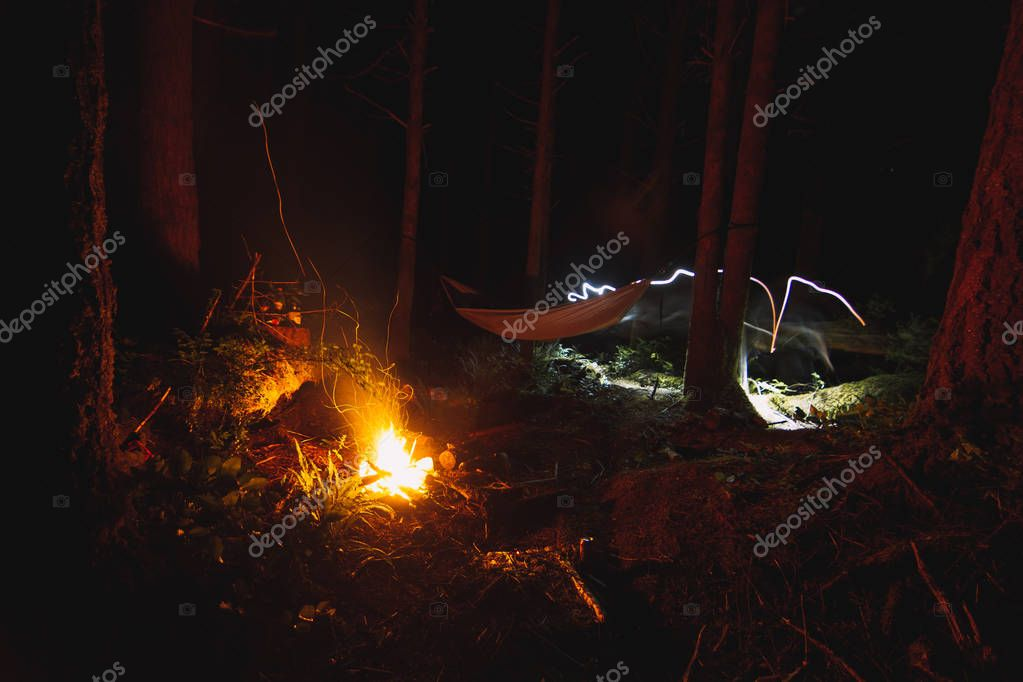 Camping in the night in the forest with hammock and campfire