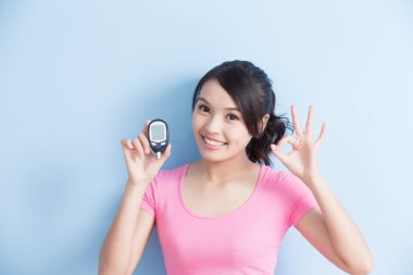woman holding  blood glucose meter
