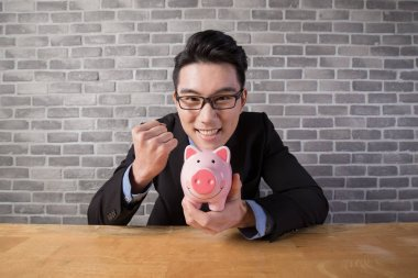 business man holding  piggy bank