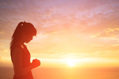 woman praying  pious with sunrise