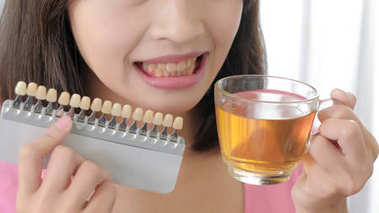 woman take teeth color palette and tea.  whiten concept