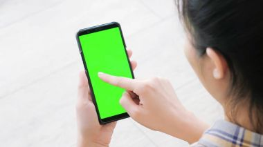 woman using  cell phone with green screen at  home