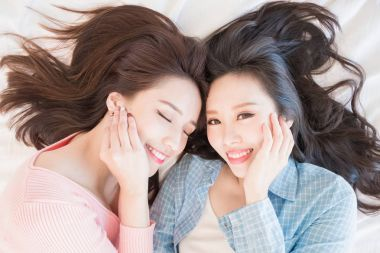 two beauty women smiling  happily and lying on bed