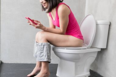 woman with  phone smiling in the toilet