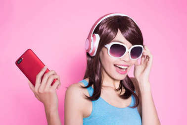 woman using  phone and listening to  music on the pink background