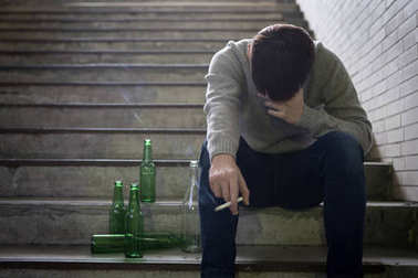 depressed man  in underground  with beer and cigarette