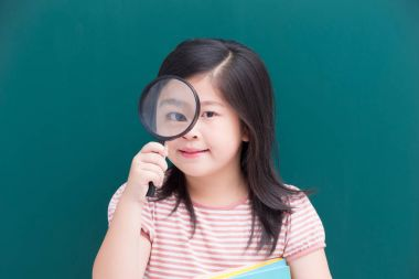 cute girl holding  magnifying with green chalkboard