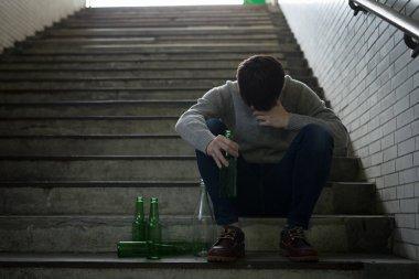 depressed man with alcoholism problem  sitting  underground