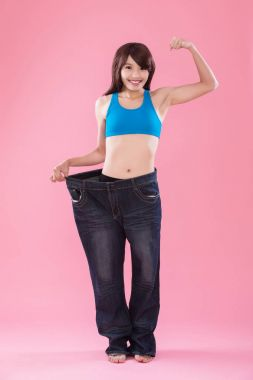 woman wearing  jeans and showing  weight loss on the pink background