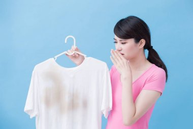 woman smelling dirty shirt on the blue background