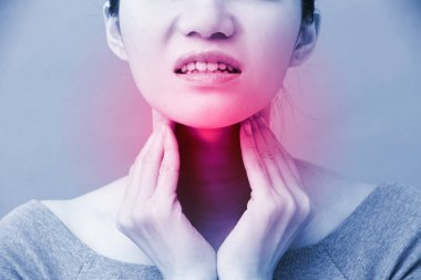 women with thyroid gland problem on the grey background