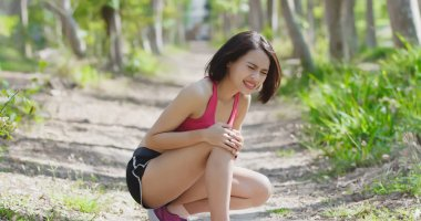 sport woman feeling  pain from  knee injury in the forest