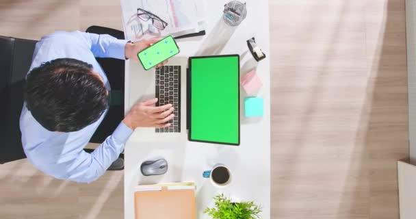 férfi használ okostelefon és laptop