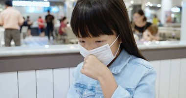 little asian girl wear face mask and cough indoor because of transmissible infectious diseases or air pollution in the crowd