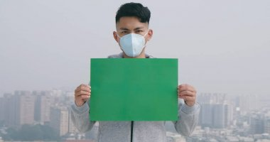 asian man hold green copy space billboard and wears protective face mask against transmissible infectious diseases or air pollution in the city