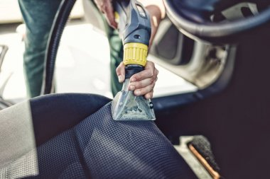 Close up details of car steats vacuuming using steaming tools