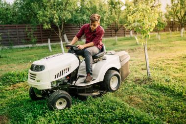 Handsome man, worker using grass cutting equipment for landscaping works