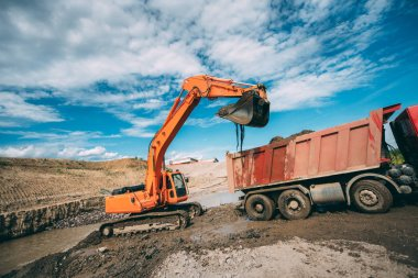 Working excavator on construction site, loading dumper truck during earthmoving works