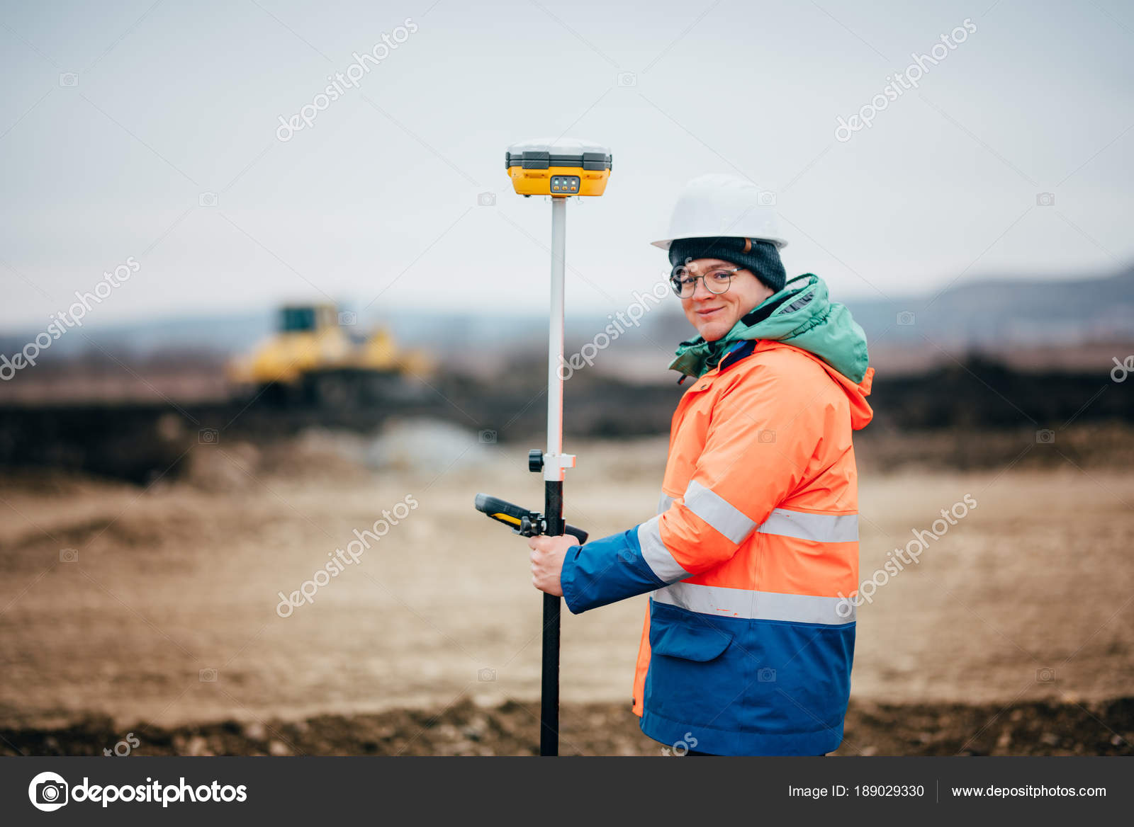 Surveyor engineer working on highway construction site, working with